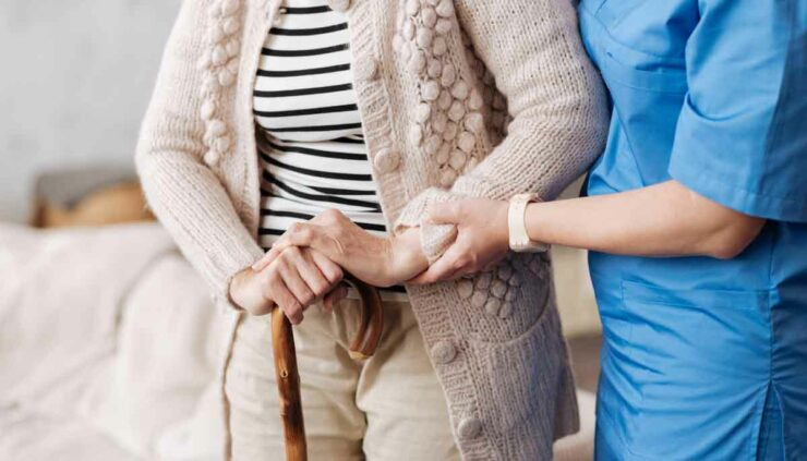 An elderly person is helped by a caregiver in a Nursing Home