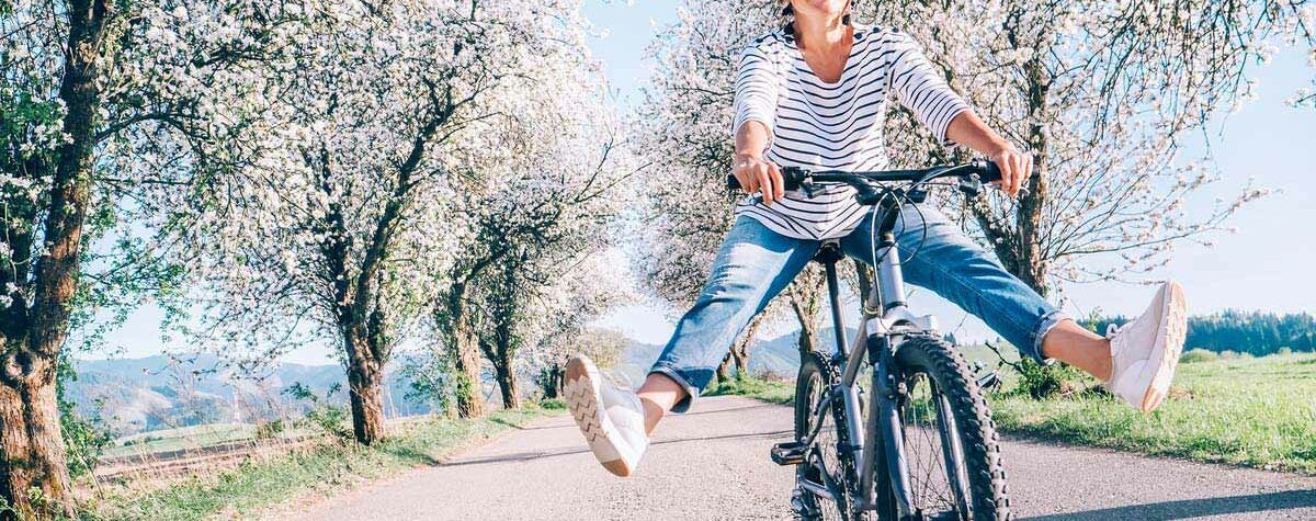 happy woman riding bicycle outside during spring