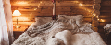 Woman holding coffee mug in air as she rests under sheets in log cabin