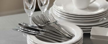 Set of clean dishware, cutlery and champagne glasses on grey table