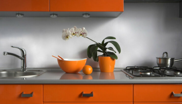 a kitchen with orange and grey colors