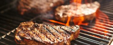 Grilling steaks over flame