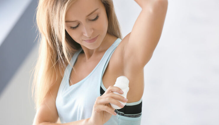 woman putting on deodorant